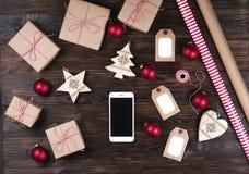 有圣诞节礼物的巧妙的电话在木背景顶视图 网上假日购物概念 平的位置,文本空间 互联网 免版税库存照片