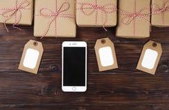 有圣诞节礼物的巧妙的电话在木背景顶视图 网上假日购物概念 平的位置,文本空间 互联网 免版税库存图片