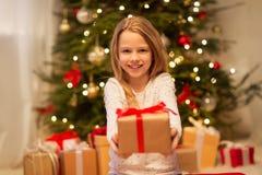 有圣诞节礼物的微笑的女孩在家 免版税库存照片
