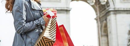 有圣诞节礼物的愉快的妇女在凯旋门附近在巴黎 库存照片