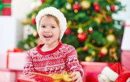 有圣诞节礼物的愉快的孩子在圣诞树附近 免版税库存图片