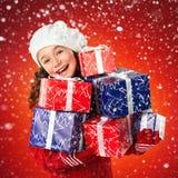 有圣诞节礼物的愉快的小女孩,新年假日销售 免版税库存图片