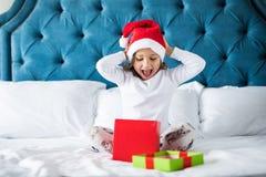 有圣诞节礼物的愉快的小孩在激动的圣诞老人帽子,当打开礼物早晨在床上时 免版税库存照片
