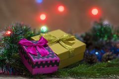 有圣诞节礼物的桃红色和橙色箱子与弓和一bokeh在背景中 库存图片