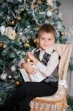 有圣诞节礼物的男孩在杉树附近 节假日 微笑 免版税库存照片