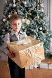 有圣诞节礼物的男孩在杉树附近 节假日 免版税库存照片