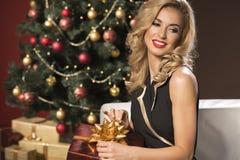 有圣诞节礼物的秀丽端庄的妇女 免版税库存照片