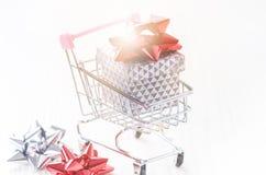 有圣诞节礼物的购物台车 有红色丝带的礼物盒在白色背景 圣诞节装饰装饰新家庭想法 免版税库存图片