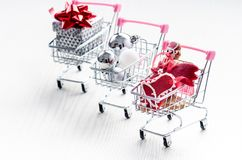 有圣诞节礼物的购物台车 有红色丝带的礼物盒在白色背景 圣诞节装饰装饰新家庭想法 库存图片