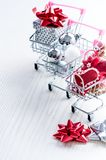 有圣诞节礼物的购物台车 有红色丝带的礼物盒在白色背景 圣诞节装饰装饰新家庭想法 免版税图库摄影