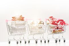 有圣诞节礼物的购物台车 有红色丝带的礼物盒在白色背景 圣诞节装饰装饰新家庭想法 库存照片