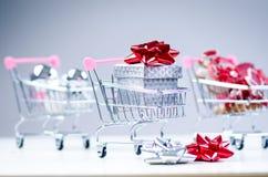 有圣诞节礼物的购物台车 有红色丝带的礼物盒在白色背景 圣诞节装饰装饰新家庭想法 免版税库存照片