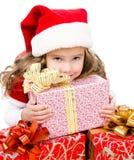 有圣诞节礼物盒和圣诞老人帽子的愉快的逗人喜爱的小女孩 图库摄影