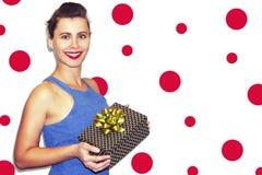 有圣诞节礼物盒的快乐的美丽的少妇,拿着礼物 深色的女孩纵向 免版税库存照片