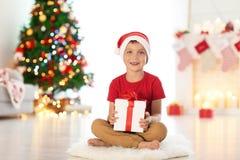有圣诞节礼物盒的愉快的小男孩在家坐地毯 免版税图库摄影