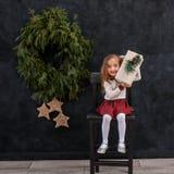 有圣诞节礼物盒的愉快的微笑的女孩 免版税库存照片