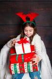 有圣诞节礼物盒的愉快的矮小的微笑的女孩 圣诞节概念 鹿垫铁的微笑的滑稽的孩子在木 免版税库存图片