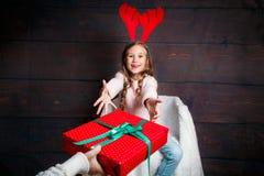 有圣诞节礼物盒的愉快的矮小的微笑的女孩 圣诞节概念 鹿垫铁的微笑的滑稽的孩子在演播室 免版税库存图片