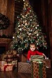 有圣诞节礼物盒的愉快的矮小的微笑的女孩 免版税库存照片