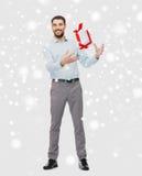 有圣诞节礼物盒的愉快的年轻人在雪 库存图片