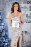 有圣诞节礼物盒的,新年树backgr年轻秀丽妇女 免版税库存照片