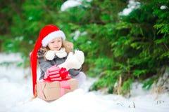 有圣诞节礼物礼物的可爱的小女孩在户外冬天自Xmas前夕 库存图片