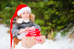 有圣诞节礼物礼物的可爱的小女孩在户外冬日 免版税库存图片
