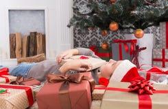 有圣诞节礼物箱子和礼物的,侧视图愉快的孩子 库存图片