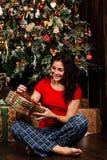 有圣诞节礼物箱子的妇女在背景装饰了圣诞树 一件红色衬衣的浅黑肤色的男人 库存图片