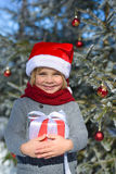 有圣诞节礼物im冬天森林的逗人喜爱的小男孩 库存图片