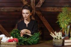 有圣诞节花圈的工作的卖花人妇女 准备圣诞节常青树花圈的年轻逗人喜爱的微笑的妇女设计师 库存图片