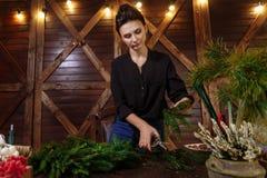 有圣诞节花圈的工作的卖花人妇女 准备圣诞节常青树花圈的年轻逗人喜爱的微笑的妇女设计师 免版税库存图片