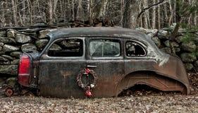 有圣诞节花圈的被放弃的老汽车 免版税库存图片