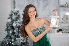 有圣诞节蜡烛的年轻秀丽妇女,新年树backgro 图库摄影