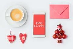 有圣诞节装饰和咖啡杯的智能手机 模板的圣诞节嘲笑 在视图之上 库存照片