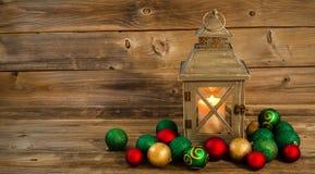 有圣诞节装饰品的发光的灯笼在土气木头 库存照片