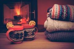 有圣诞节装饰品的杯在壁炉附近 在被编织的布料的杯子 库存照片