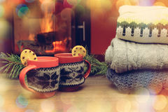 有圣诞节装饰品的杯在壁炉附近 在被编织的布料的杯子 免版税库存照片