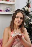 有圣诞节装饰品的美丽的女孩在手上  免版税库存照片