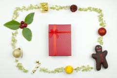 有圣诞节装饰框架的一个红色礼物盒 平的位置 免版税图库摄影