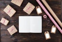 有圣诞节装饰的在木背景的笔记本和礼物 做名单,圣诞老人信件概念 顶视图,平的位置,文本spac 库存照片