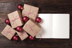 有圣诞节装饰的在木背景的笔记本和礼物 做名单,圣诞老人信件概念 顶视图,平的位置,文本spac 图库摄影