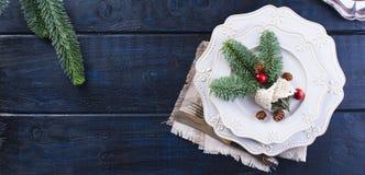 有圣诞节装饰的服务板材,在蓝色木背景 免版税库存图片
