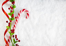 有圣诞节装饰的棒棒糖在斯诺伊背景 免版税库存照片