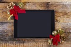 有圣诞节装饰的片剂个人计算机在木头 库存图片