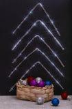 有圣诞节装饰的箱子和从闪亮金属片的抽象冷杉木 免版税库存图片