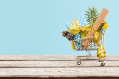 有圣诞节装饰的购物车在蓝色背景的木头 免版税库存图片