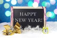 有圣诞节装饰的黑板在白色雪和与文本`新年快乐`的发光的蓝色背景 免版税库存照片