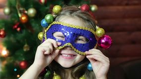 有圣诞节诗歌选的一个女孩在她的在狂欢节面具的头 股票录像