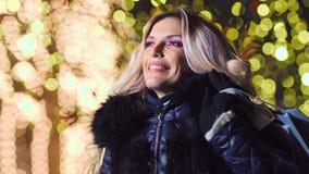 有圣诞节购物带来礼物的令人惊讶的美女在轻的bokeh照亮的背景 股票视频